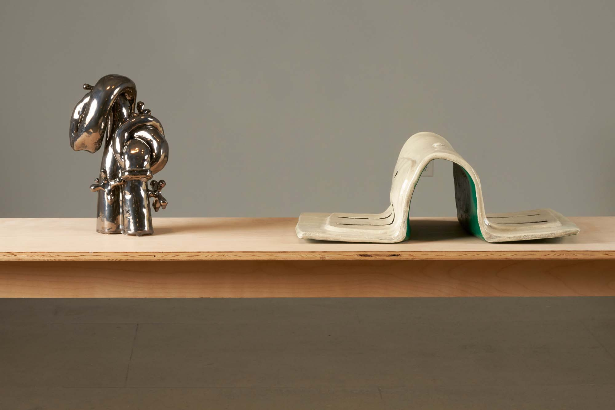 """Image of two sculptures on a tabletop, """"Outward and Bound"""" (left) and """"Out Let"""" (right) by Woody De Othello."""