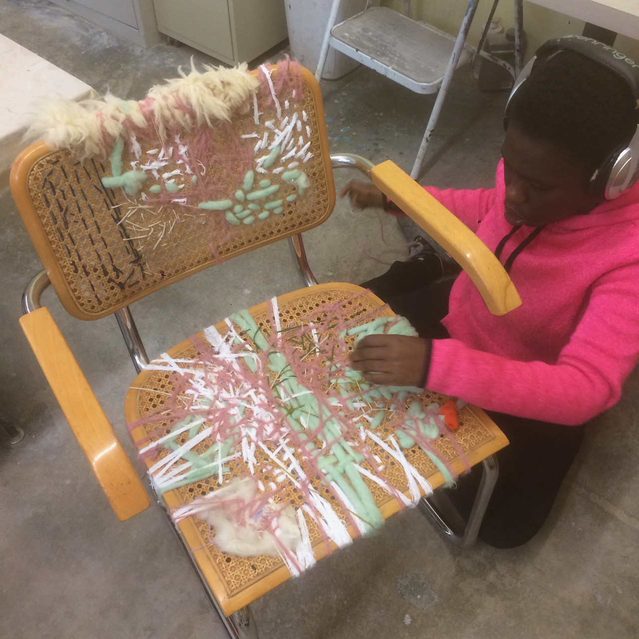 Woman in bright pink short kneeling on the ground weaving fibers into rattan chair
