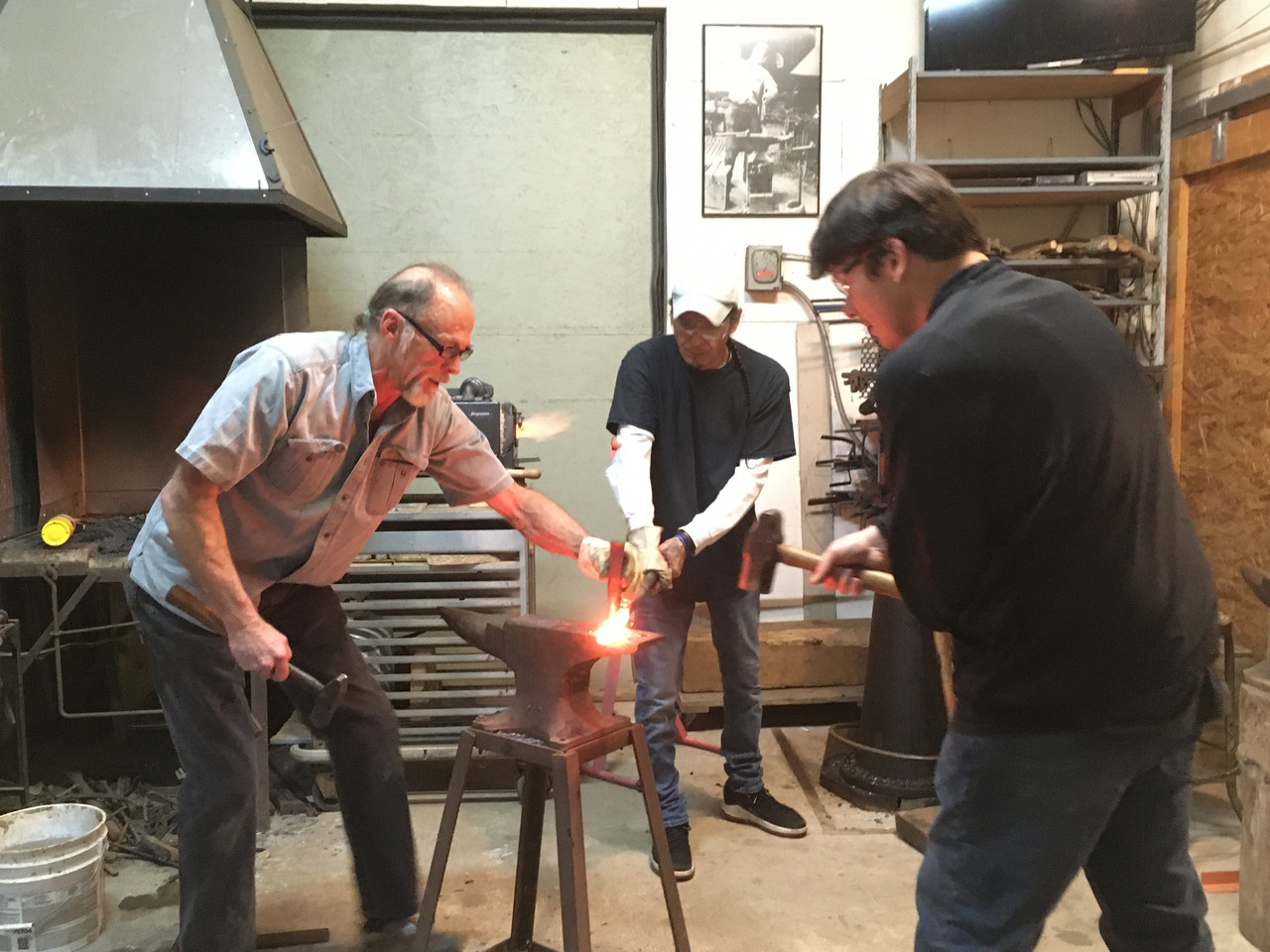 a group of three people working together to forge metal