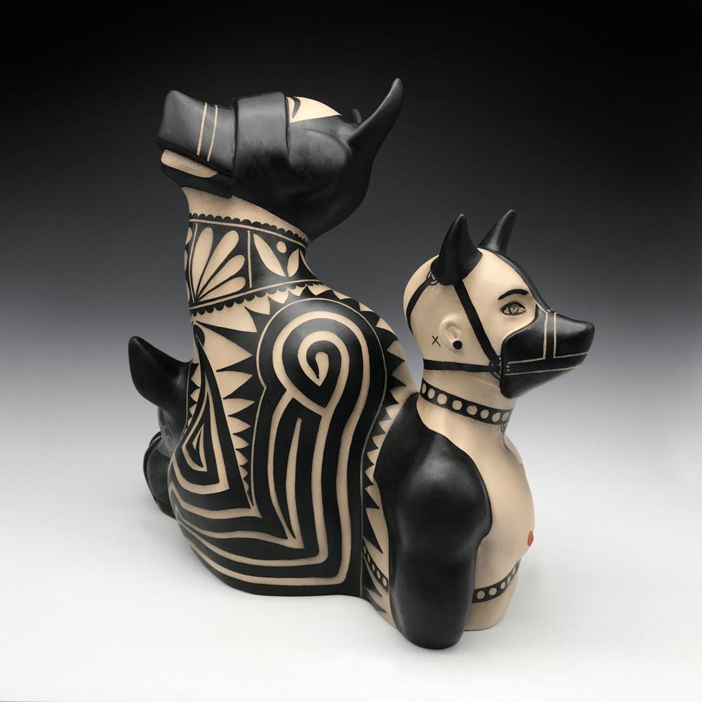 sculpture of dogs in muzzles and bondage attire.