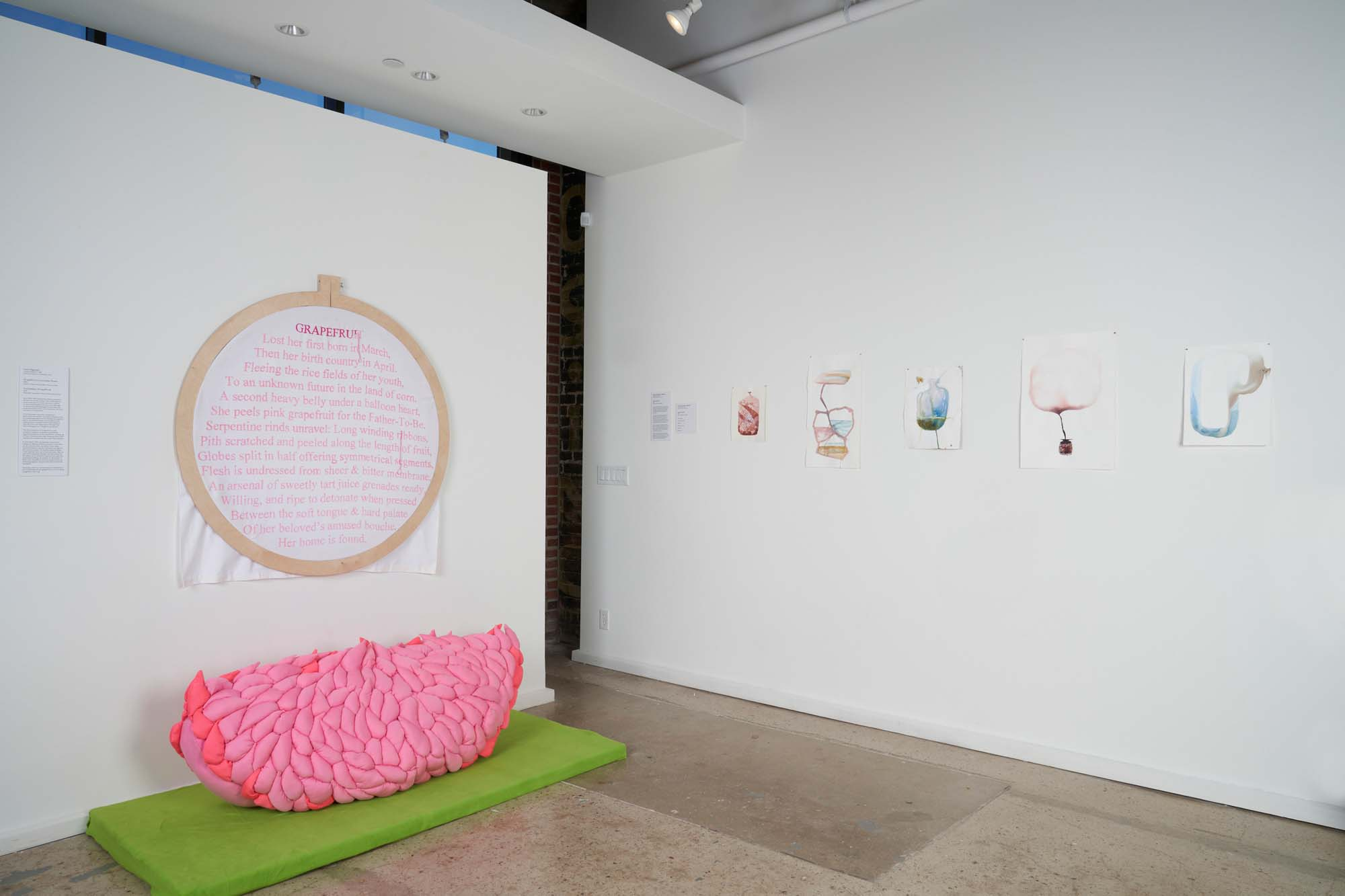 exhibition image including a large stuffed citrus on the floor and a large loom with wording inside.
