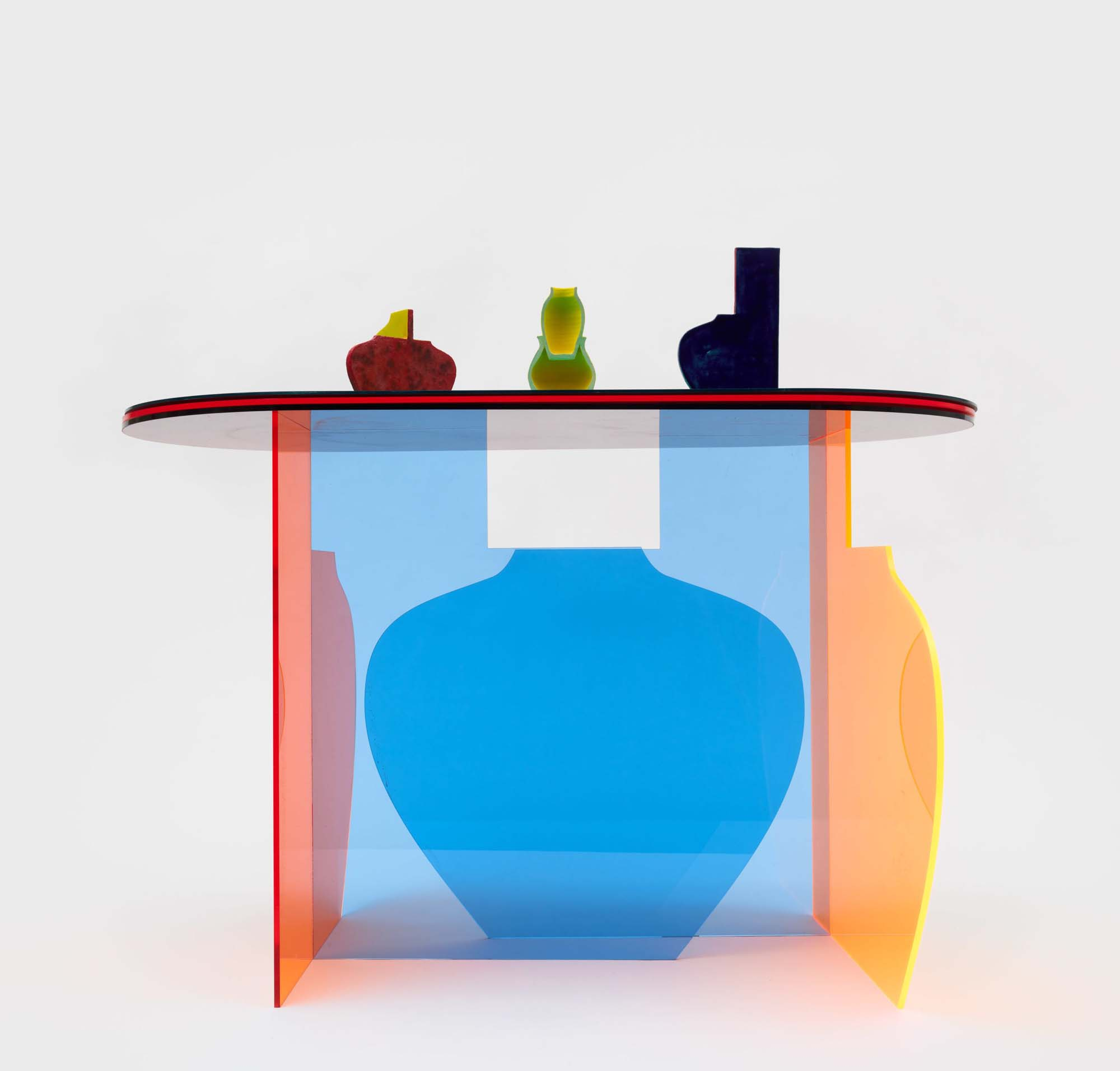 colorful see-through table with ceramic wares on top