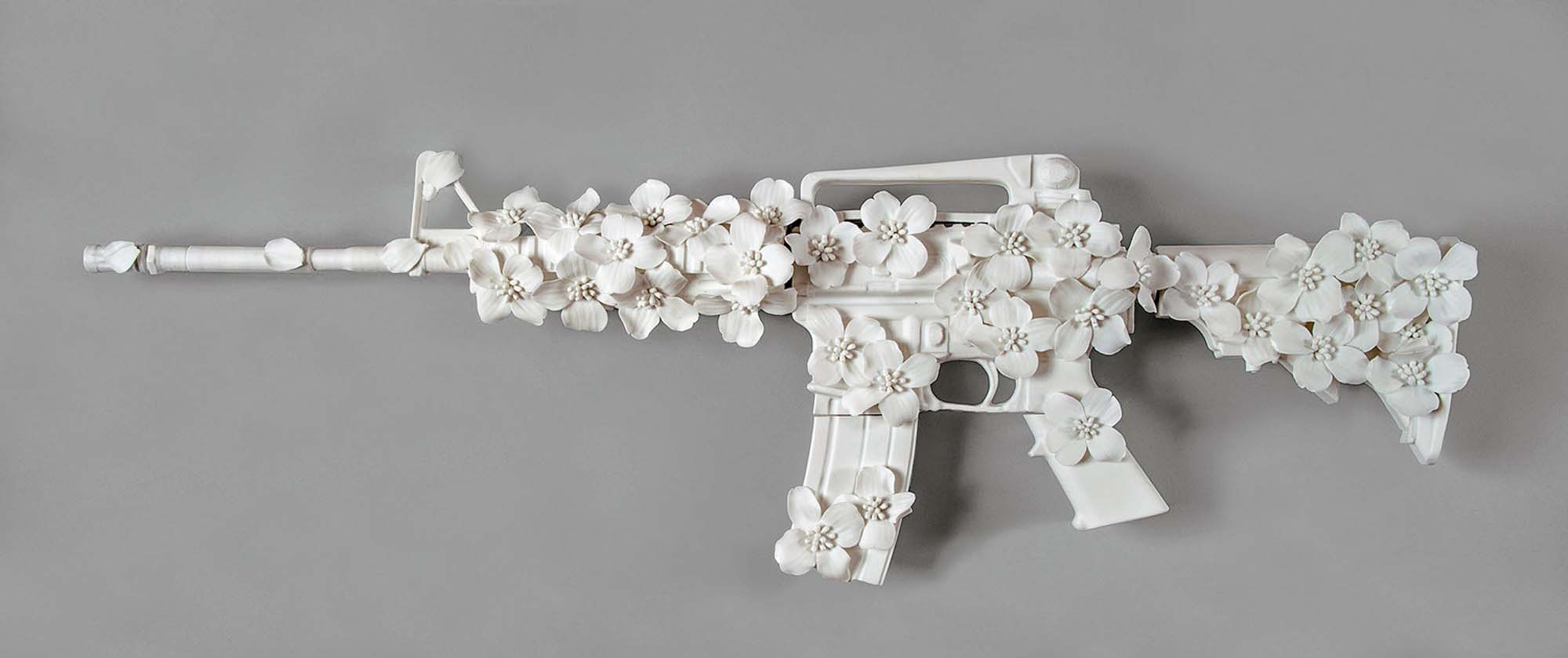 porcelain sculpture of an ar-15 rifle covered in porcelain flowers