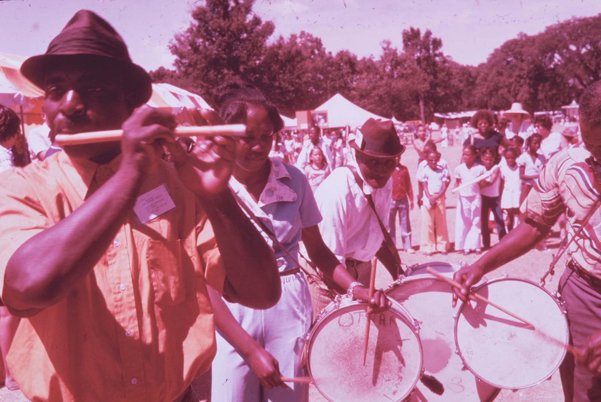 Photo of drummers at 1974 Festival of American Folklife. Photo is old and has a purple hue from aging.