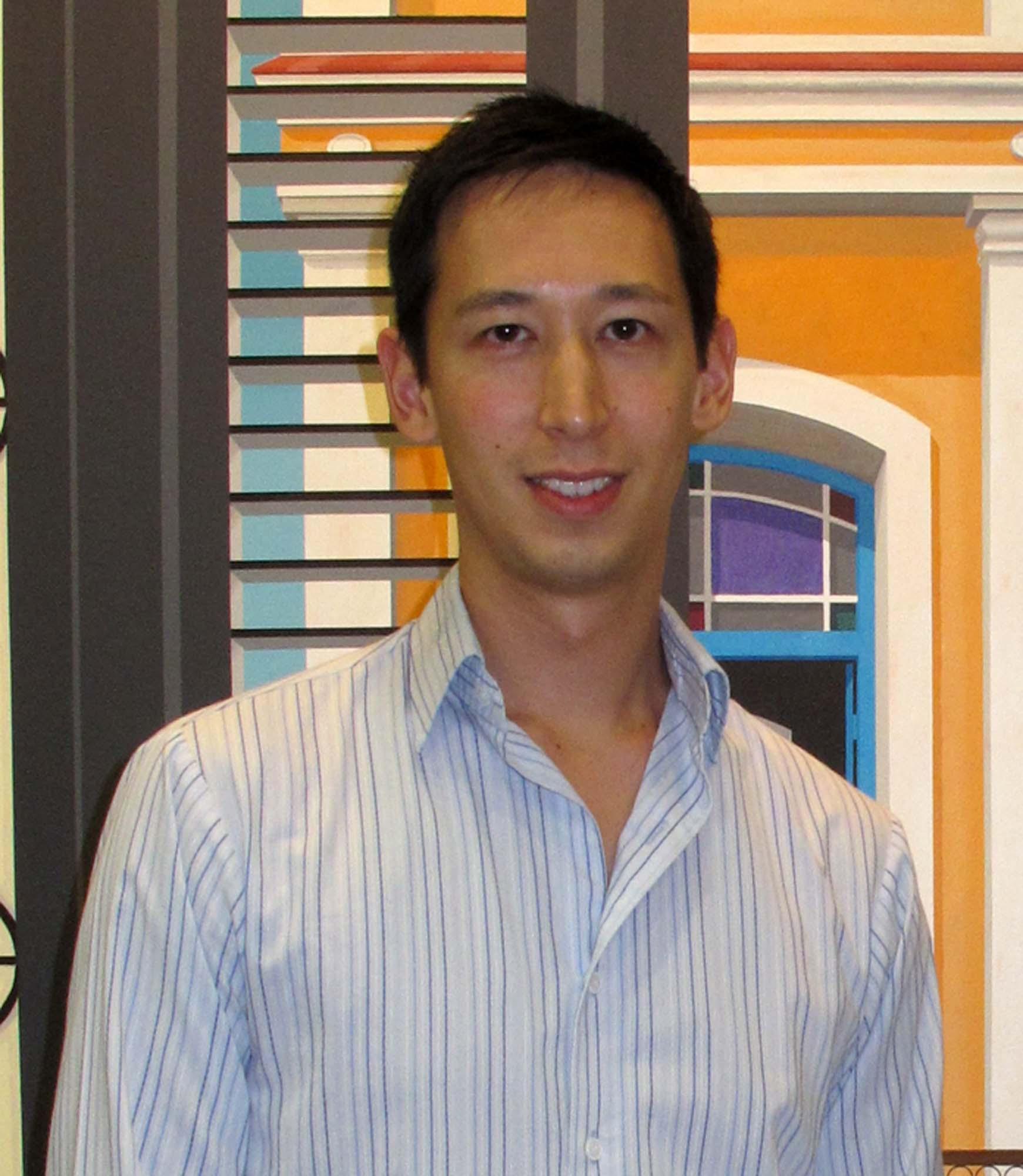 headshot of a man in a button down blue shirt