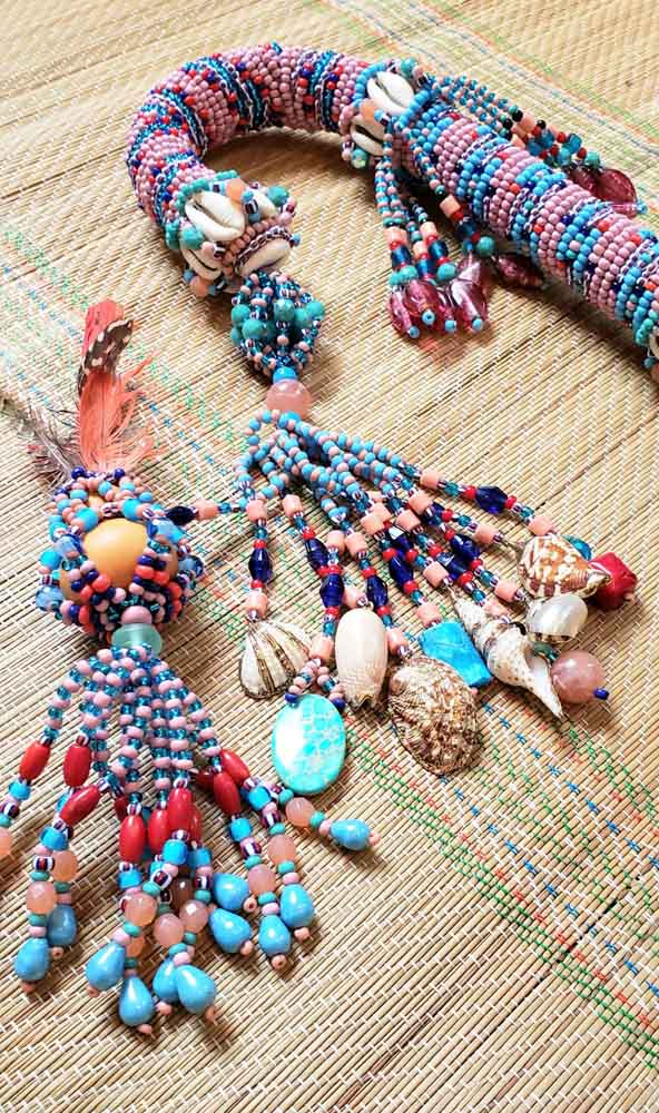 close up of beaded cane staff on bamboo mat