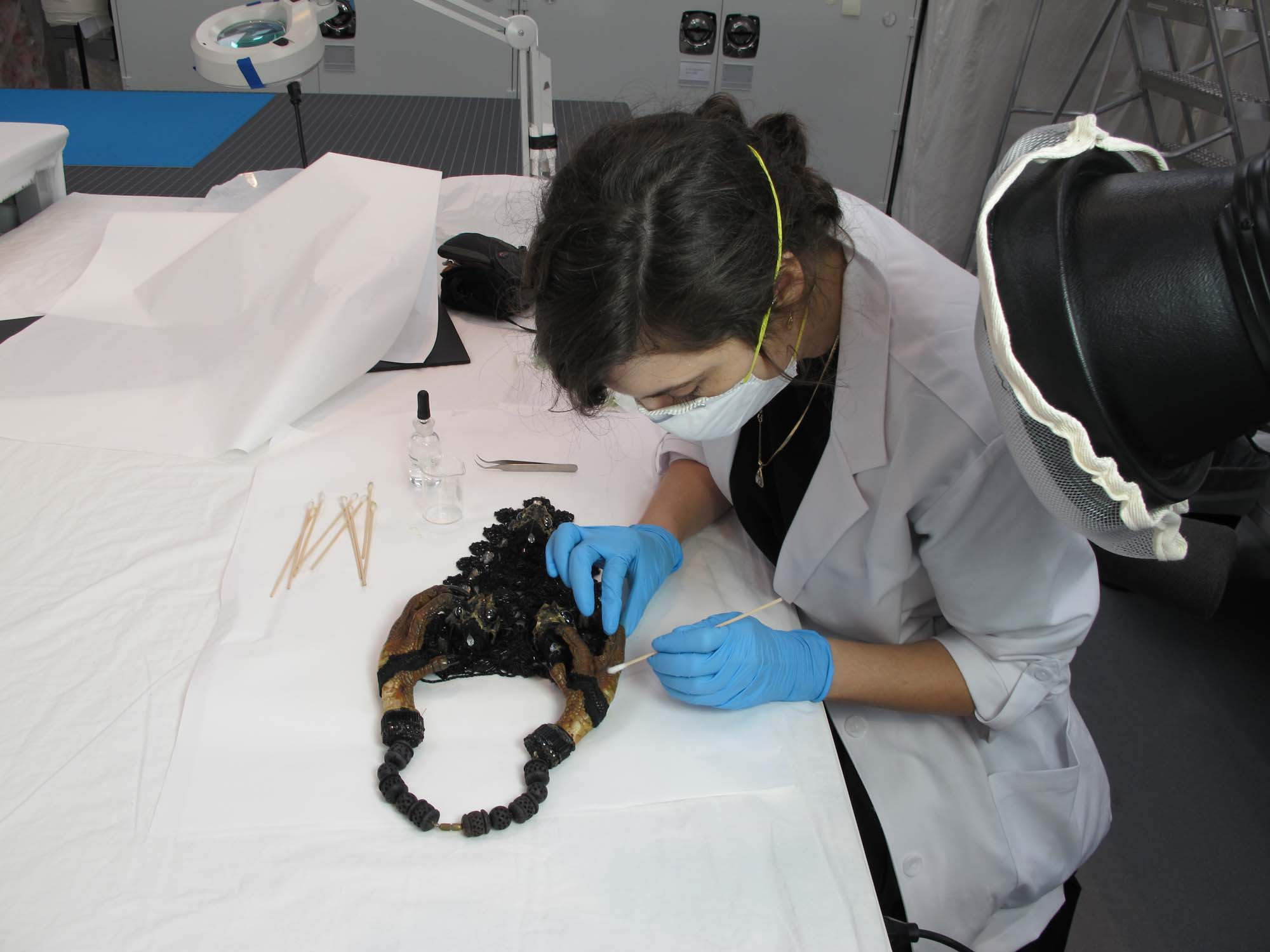 woman cleaning necklace as a museum conservator