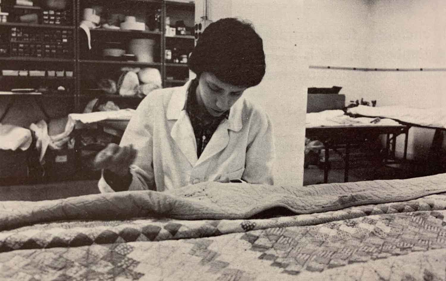 black and white image of woman preserving and conserving a textile
