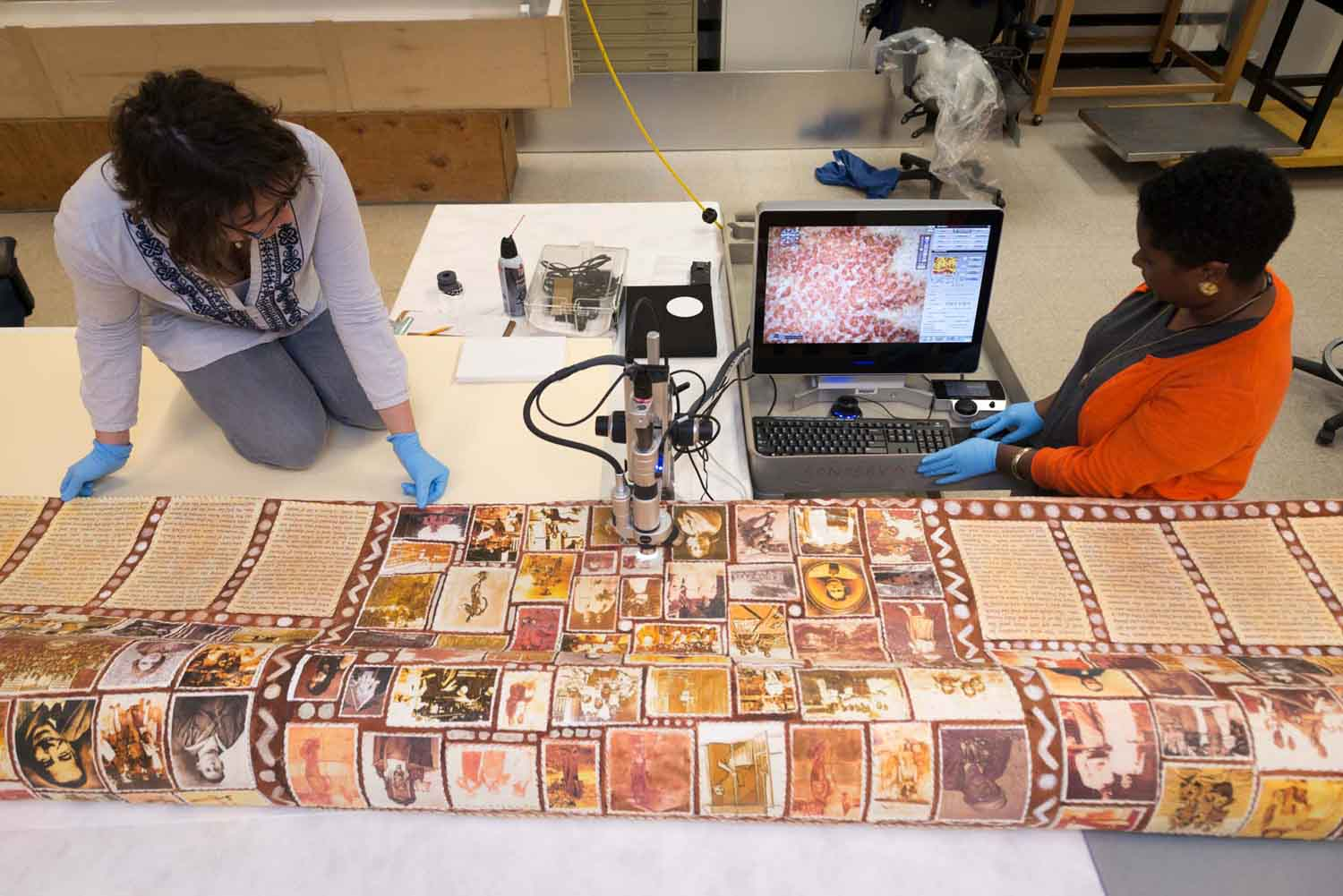two conservators using a high magnification camera to observe a textile