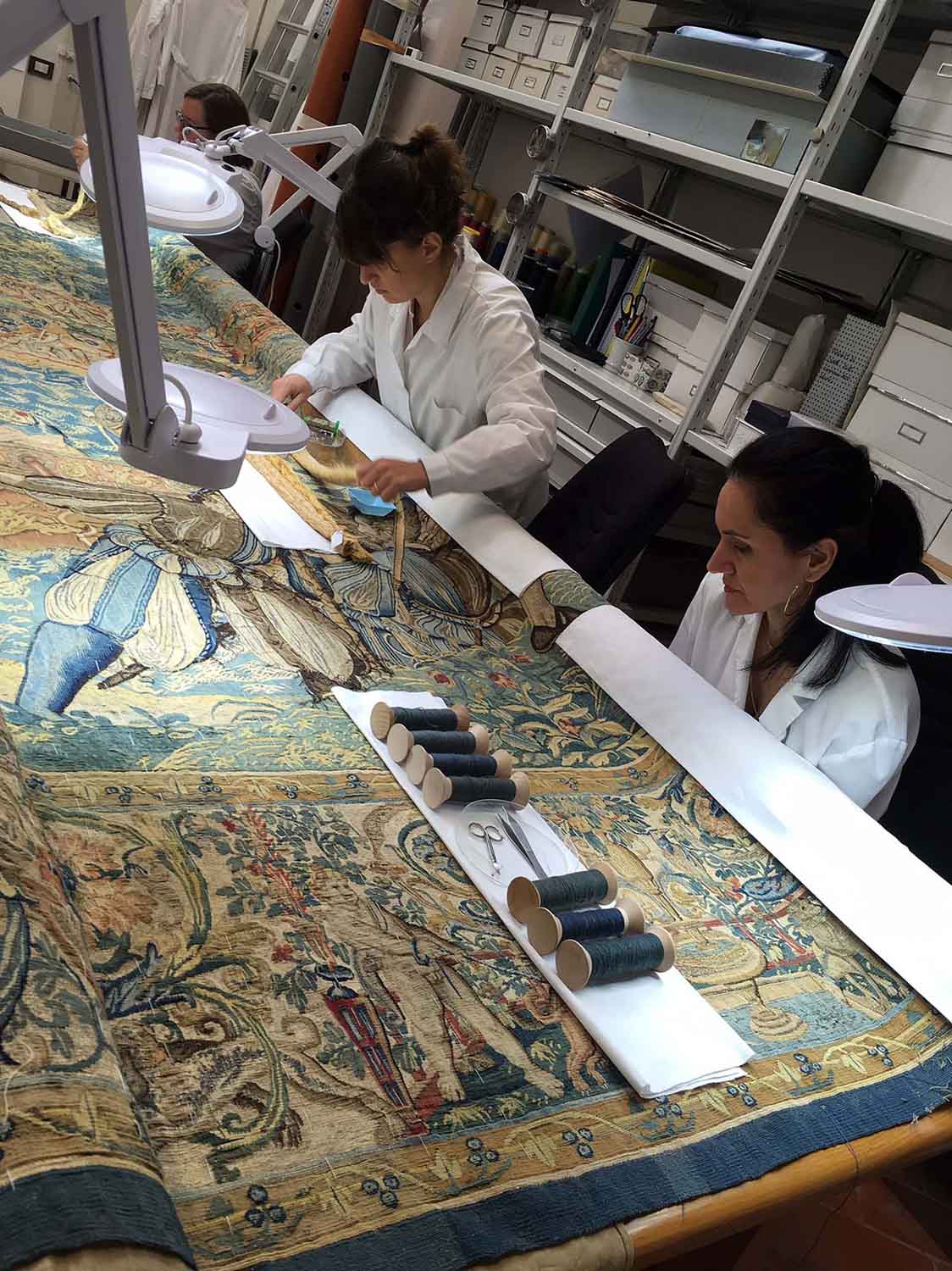 conservators working on a textile with large magnifying device