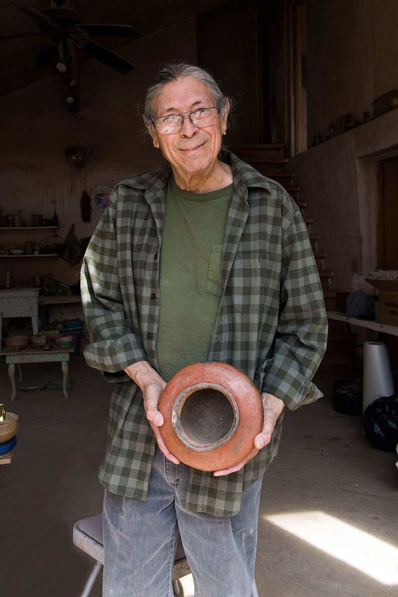 person smiling and holding a clay pot