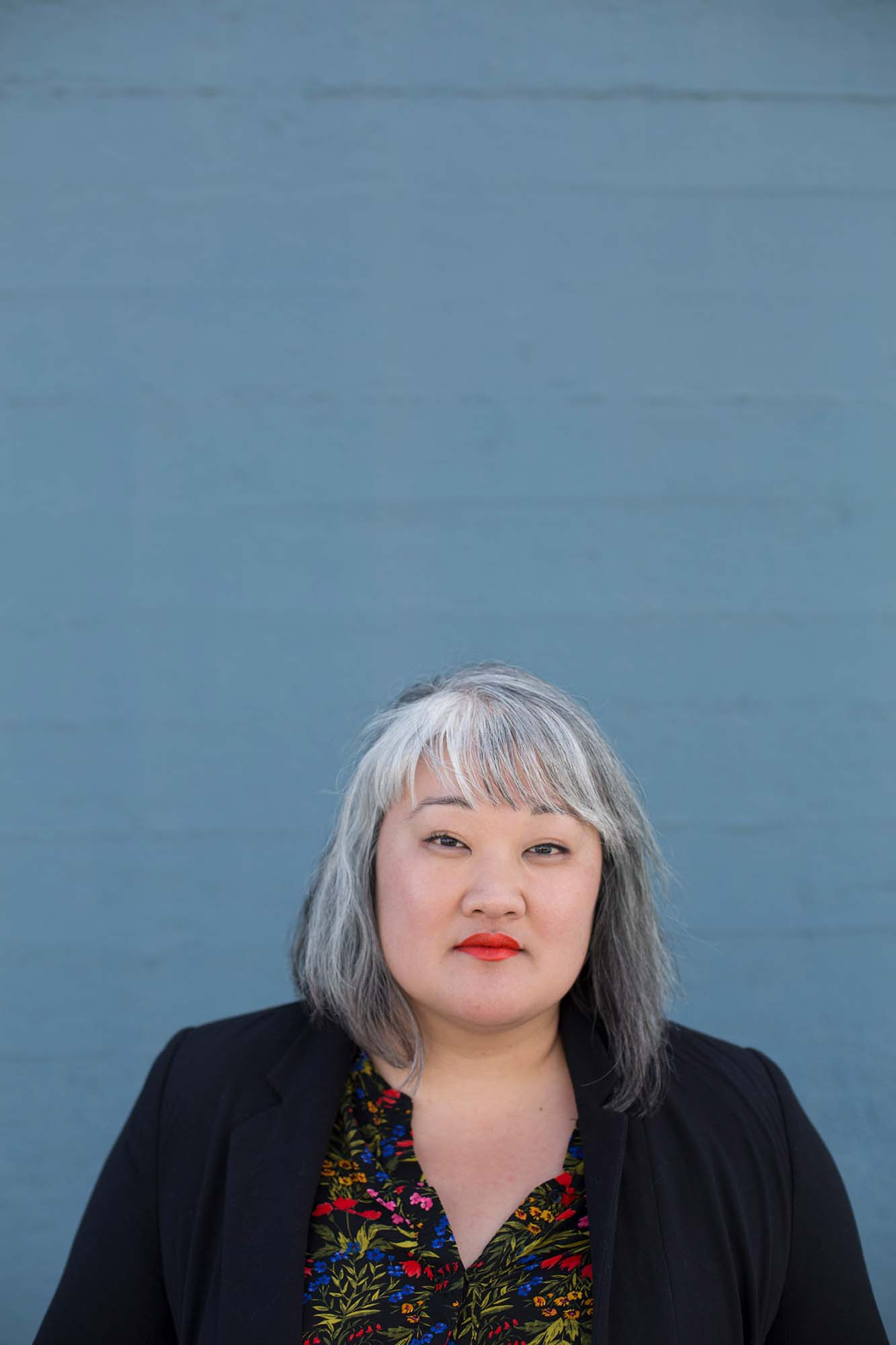 headshot of a woman with short grey hair in front of a blue wall