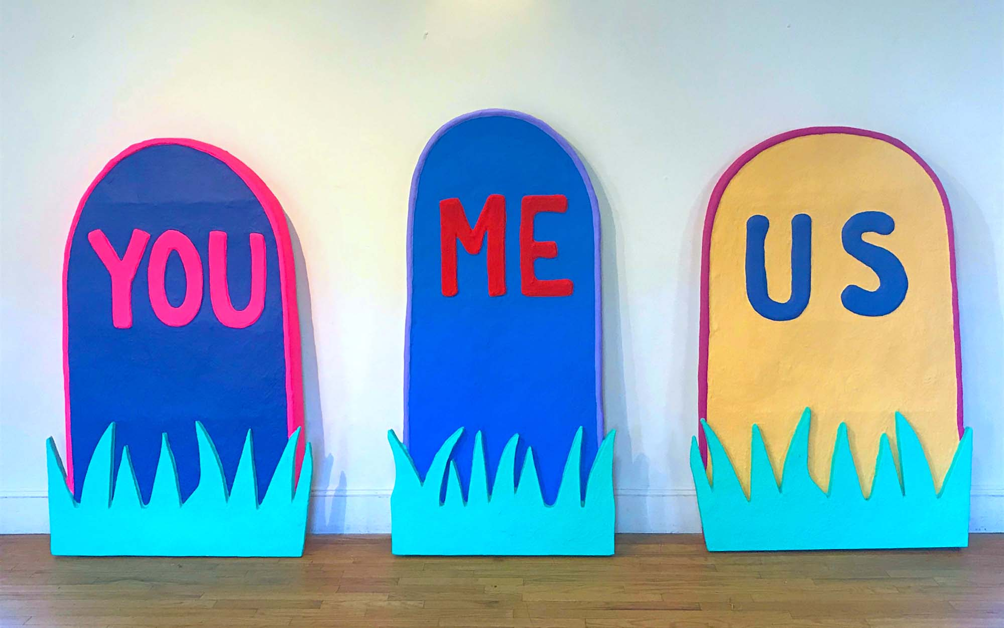 "colorful tombstone-shaped art pieces labeled ""you,"" ""me,"" and ""us"""