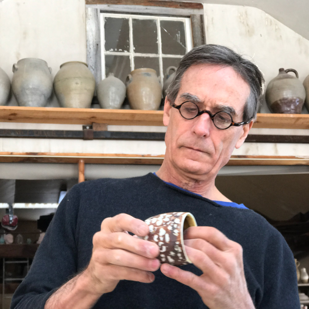 man wearing glasses working on a ceramic pot