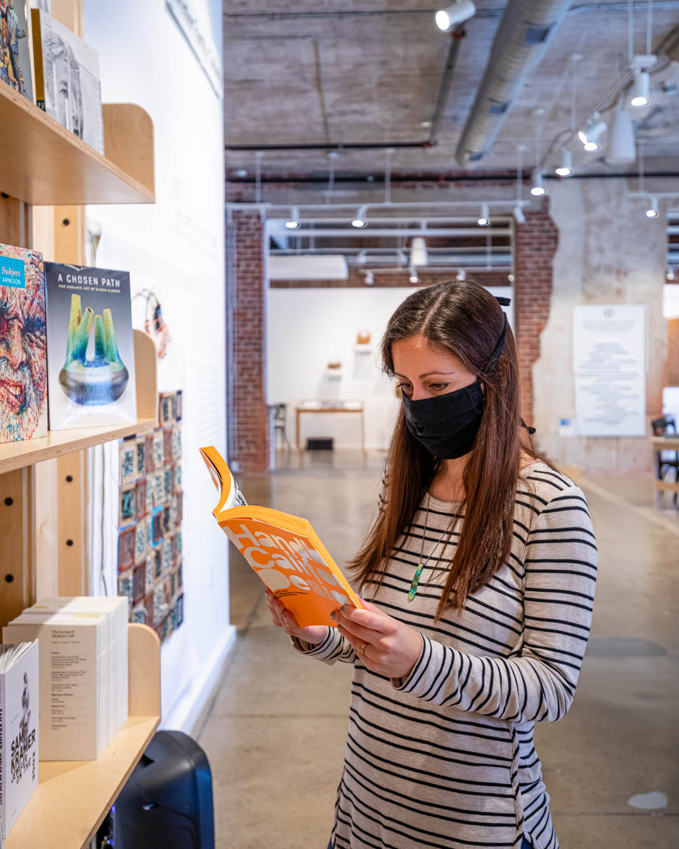 woman in striped shirt wearing a mask and reading exhibition information in gallery space at Center for Craft