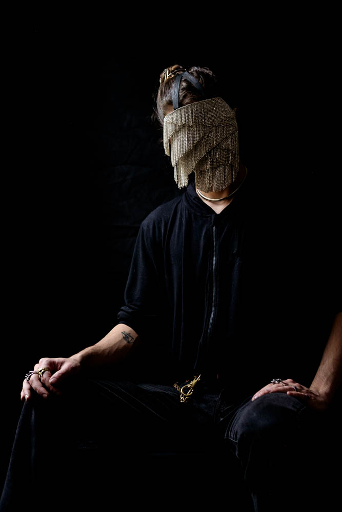 A person wearing a chain mask that covers their whole face. Person sitting in a chair with a dark background.