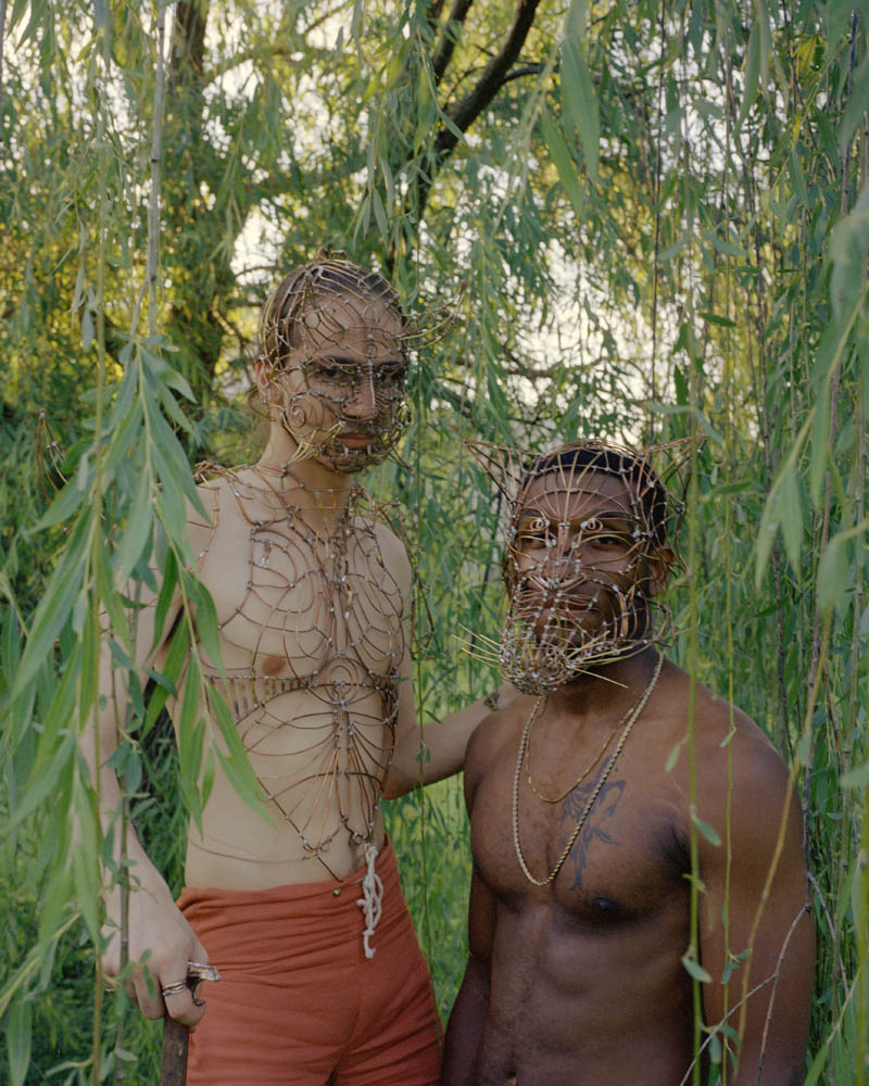 Two people side-by-side in the woods, wearing copper, brass, and tin masks and body pieces.