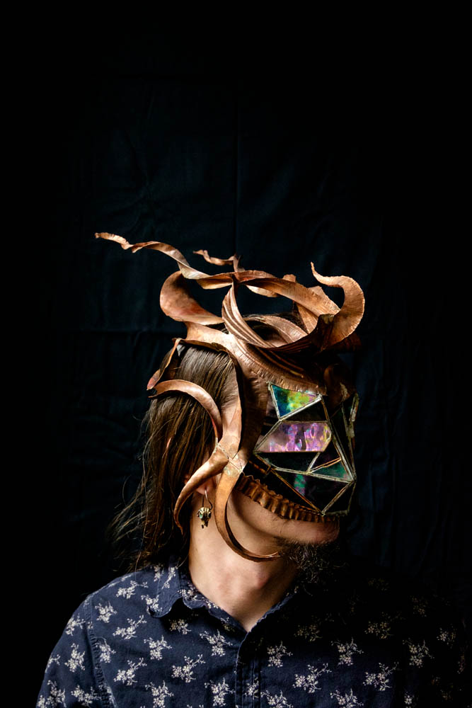 A person modeling a copper and stained glass mask in front of a dark backdrop.