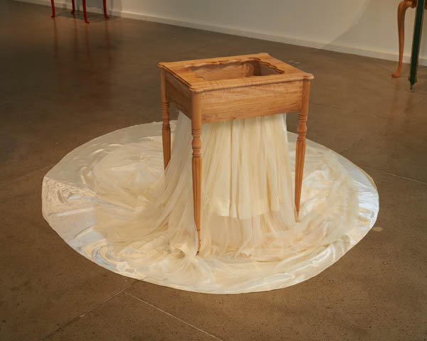 From Suite Américaine exhibition at Center for Craft, a wood table with a textile spilling out.