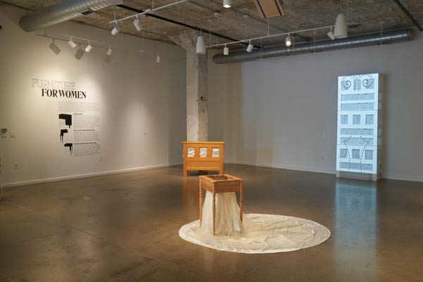 From Suite Américaine exhibition at Center for Craft, a wood chest with a textile spilling out in the center of a gallery. In the background, a tall wood chest with a projection displayed over top. On the wall also in the background, a decal about the exhibition is on the white wall.