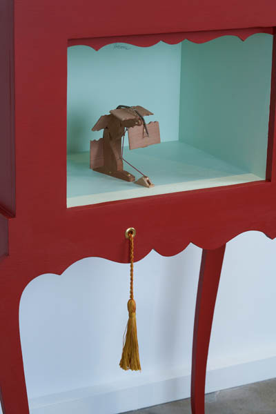 A red chest with a diorama inside, and a pulley string coming out the front.