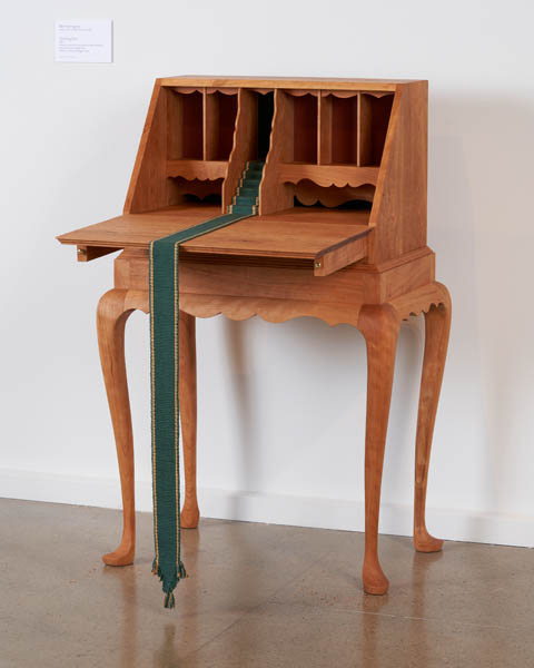 A writing desk with a little staircase in the center, with a small woven runner going down the tiny steps, across the front of the desk, then hanging down the front nearly to the floor.