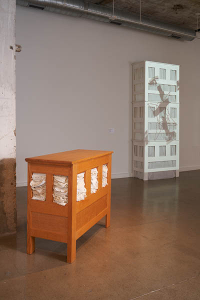 Gallery exhibition showing two large chests, one brown one in the foreground, and a white very tall one in the background. The white one has a projection of a video on it.