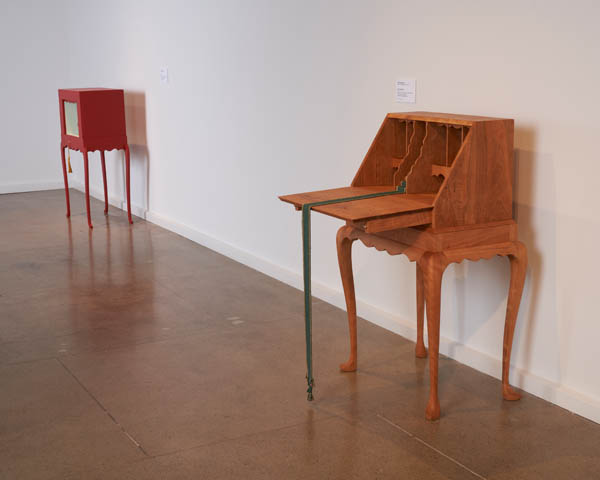 Gallery exhibition showing two pieces of handmade furniture, one brown one in the foreground, and a red one in the background. Both by BA Harrington, Craft Research Fund Artist Fellow.