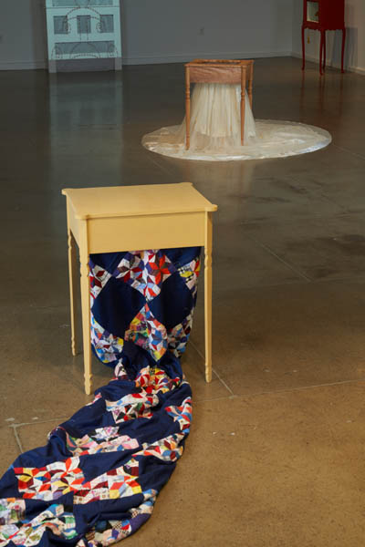 Gallery exhibition showing two pieces of handmade furniture, one tan one in the foreground with a quilt coming out of the bottom, running along the floor like a dress train. Another one in the background has a real wedding dress coming out of the bottom. Both by BA Harrington, Craft Research Fund Artist Fellow.