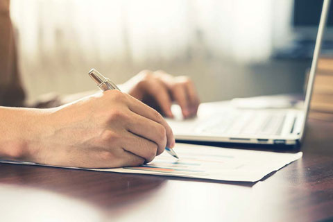 conveyancing solicitor writing on a notepad