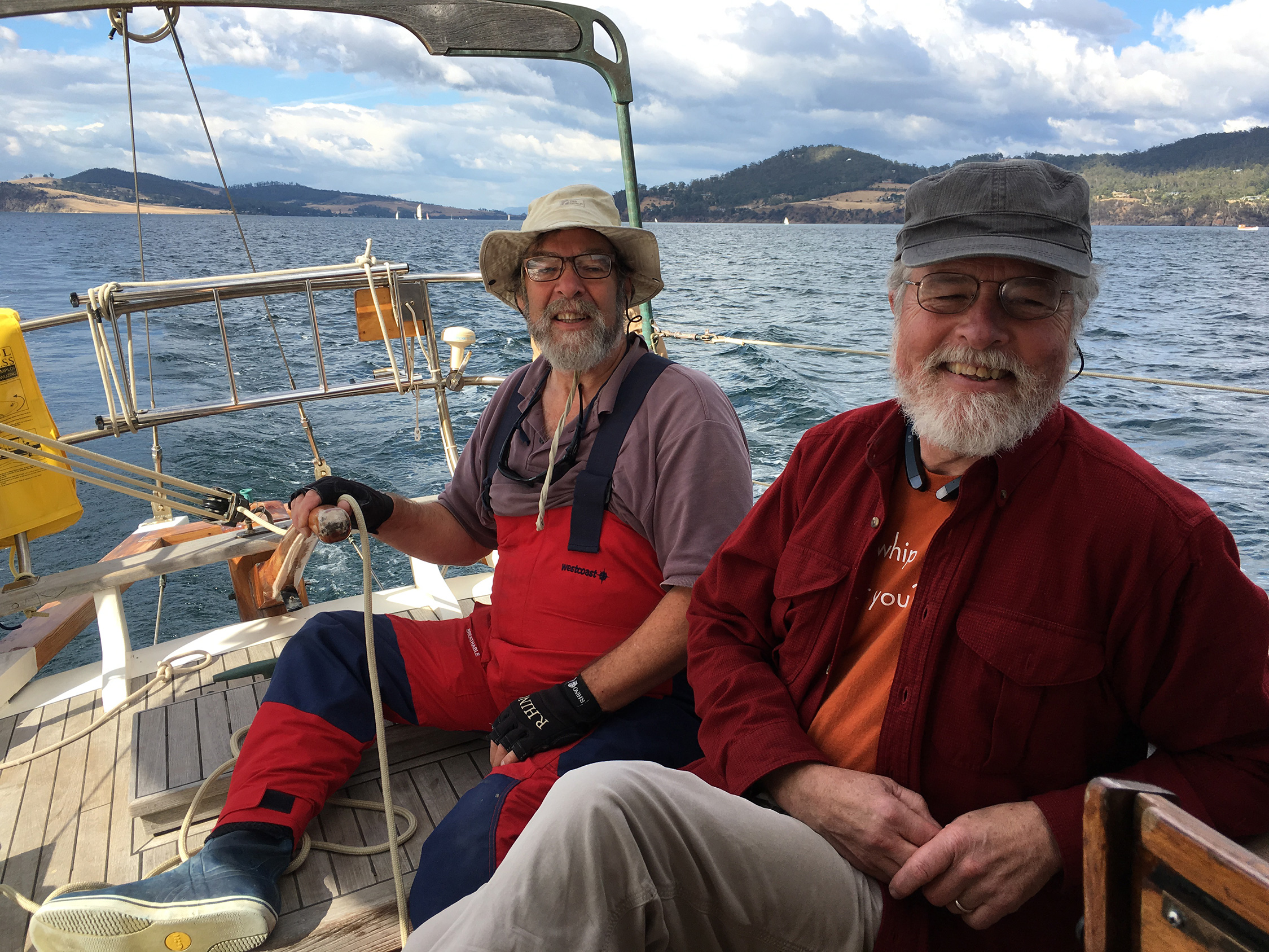 Wooden boat rigging guru Brion Toss and Pops P helming Ubique up the Channel towards Hobart