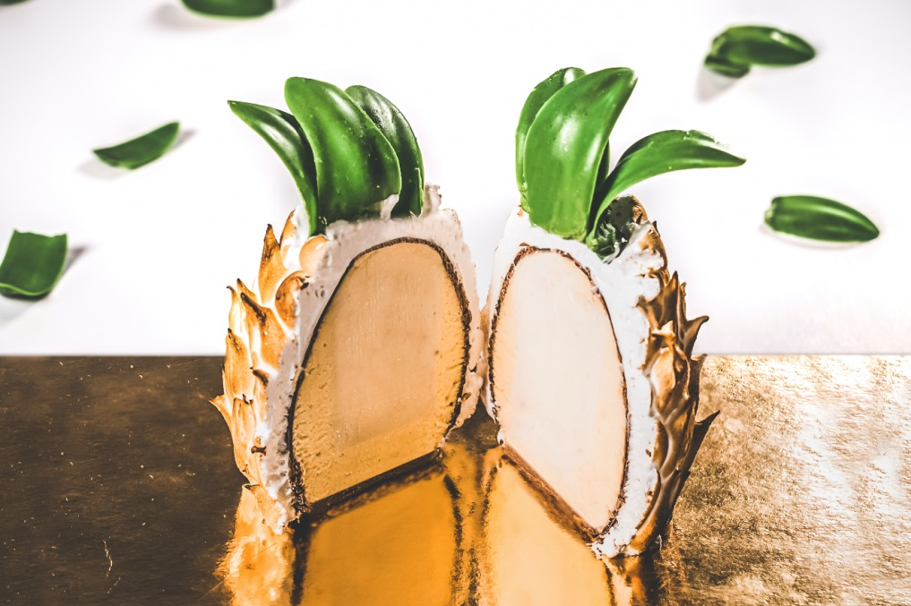 custom Pina Banana gelato cake - Banana and miso gelato is surrounded by passionfruit mousse, sitting on a bed of chocolate sponge – all enrobed in milk chocolate and finished with passionfruit Italian meringue and chocolate leaves