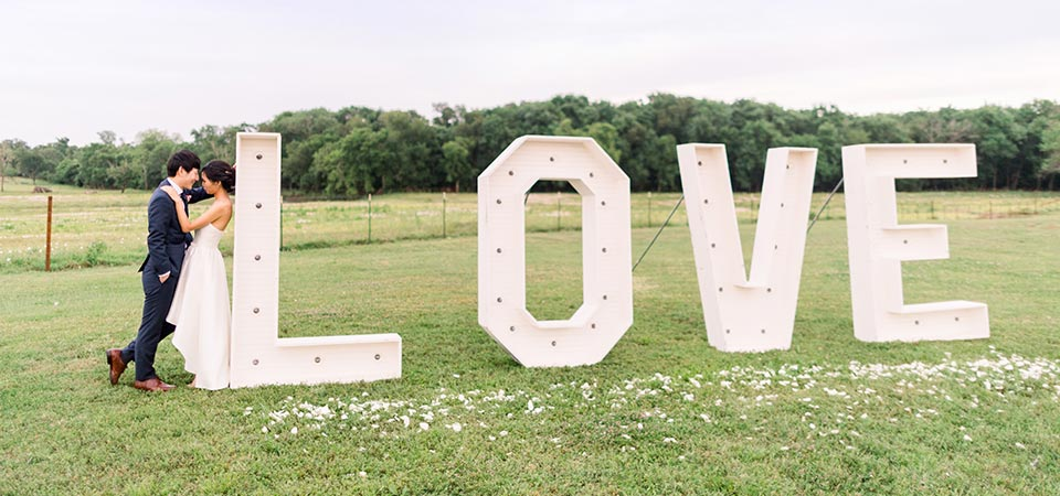 The newlyweds posing for a photo with a massive LOVE sign