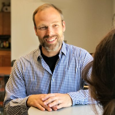 Photo of Nate Berent-Spillson: he is smiling and sitting at a table