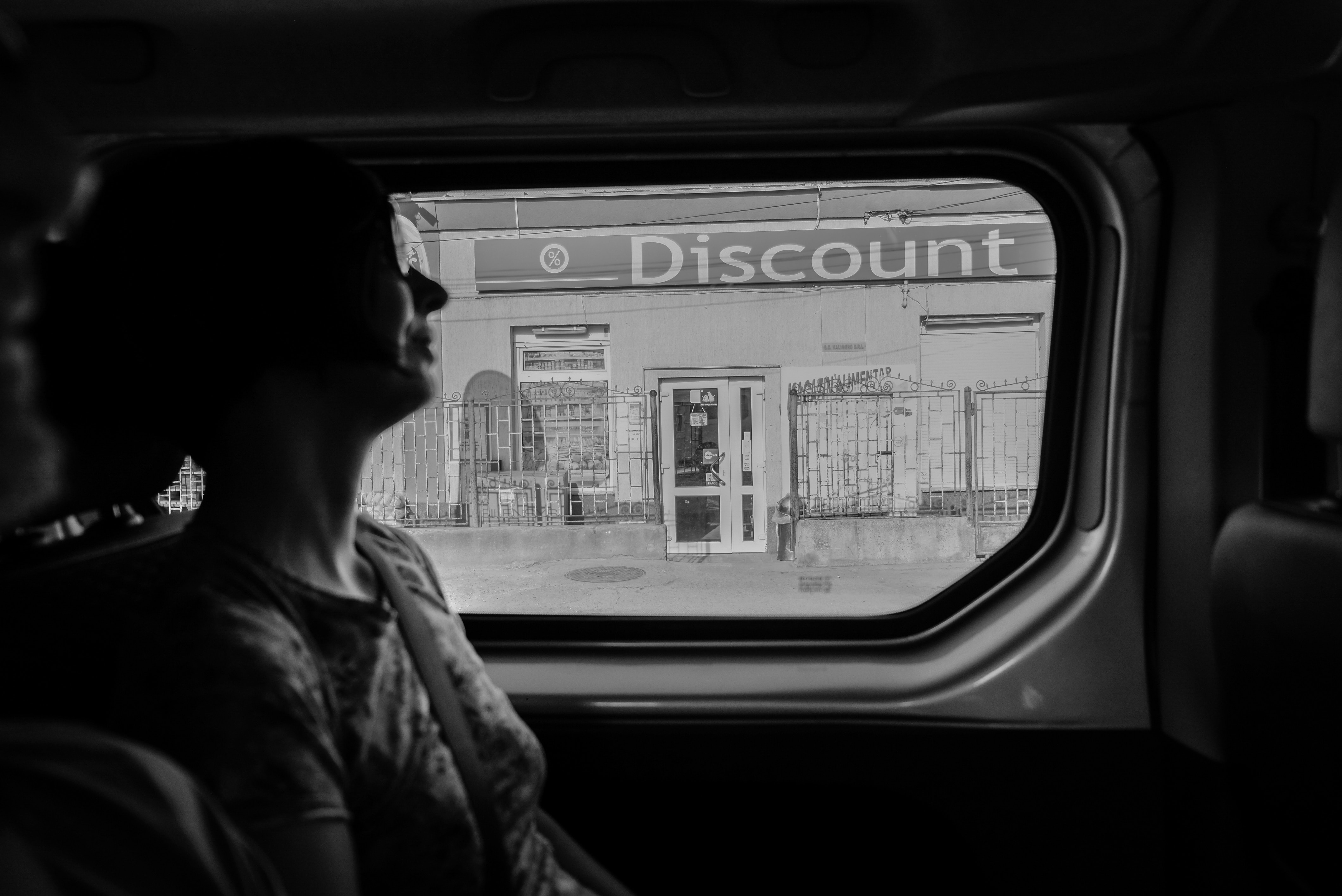 A woman looking outside a car window at a discount sign