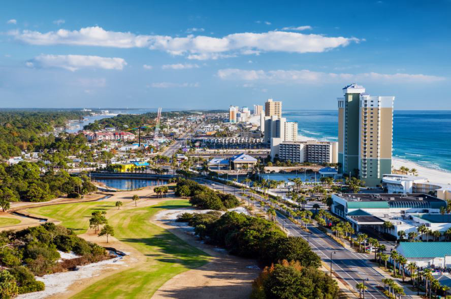 Landscape view of Panama City Beach showing a golf course, downtown buildings, and the beach of the Gulf of Mexico