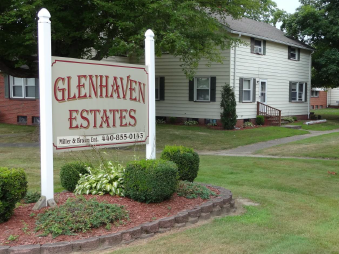 """Large white sign reading """"Glenhaven Estates"""" on a landscaped property with housing in the background"""