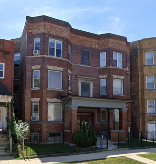 Weathered three story brick apartment building with a black fence in front of a sidewalk.