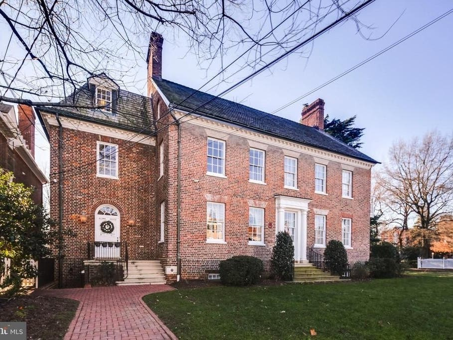 Historic brick and shingle roof building with two white doors and eleven windows showing.