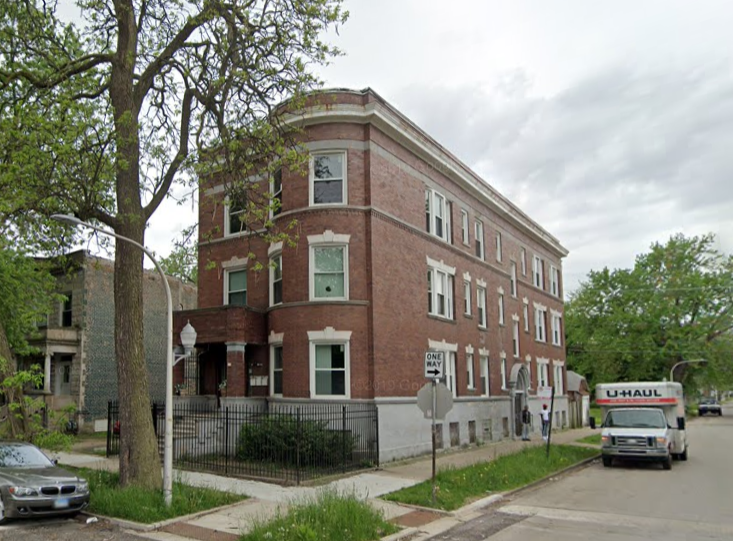 Long brick apartment building at the corner of a street with a curved front wall.