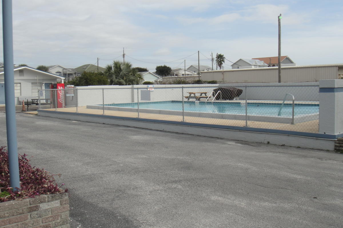 Motel pool surrounded by cement walls and a fence