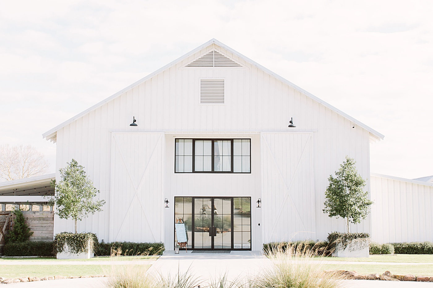 A clean white farmhouse with a glass door in a scenic setting of grassy fields.