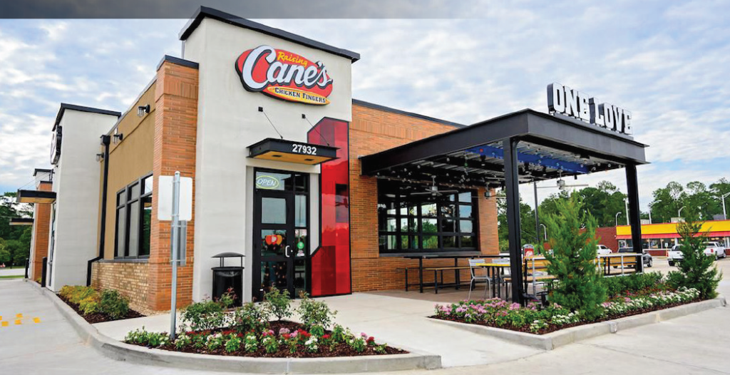 """Raising Cane's restaurant with covered outdoor seating, a drive-through window, and the Raising Cane's logo with the subtext """"Chicken Fingers""""."""