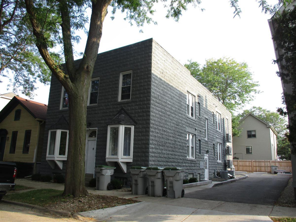 Gray two-story cinder block apartment building with white trim windows and doors.