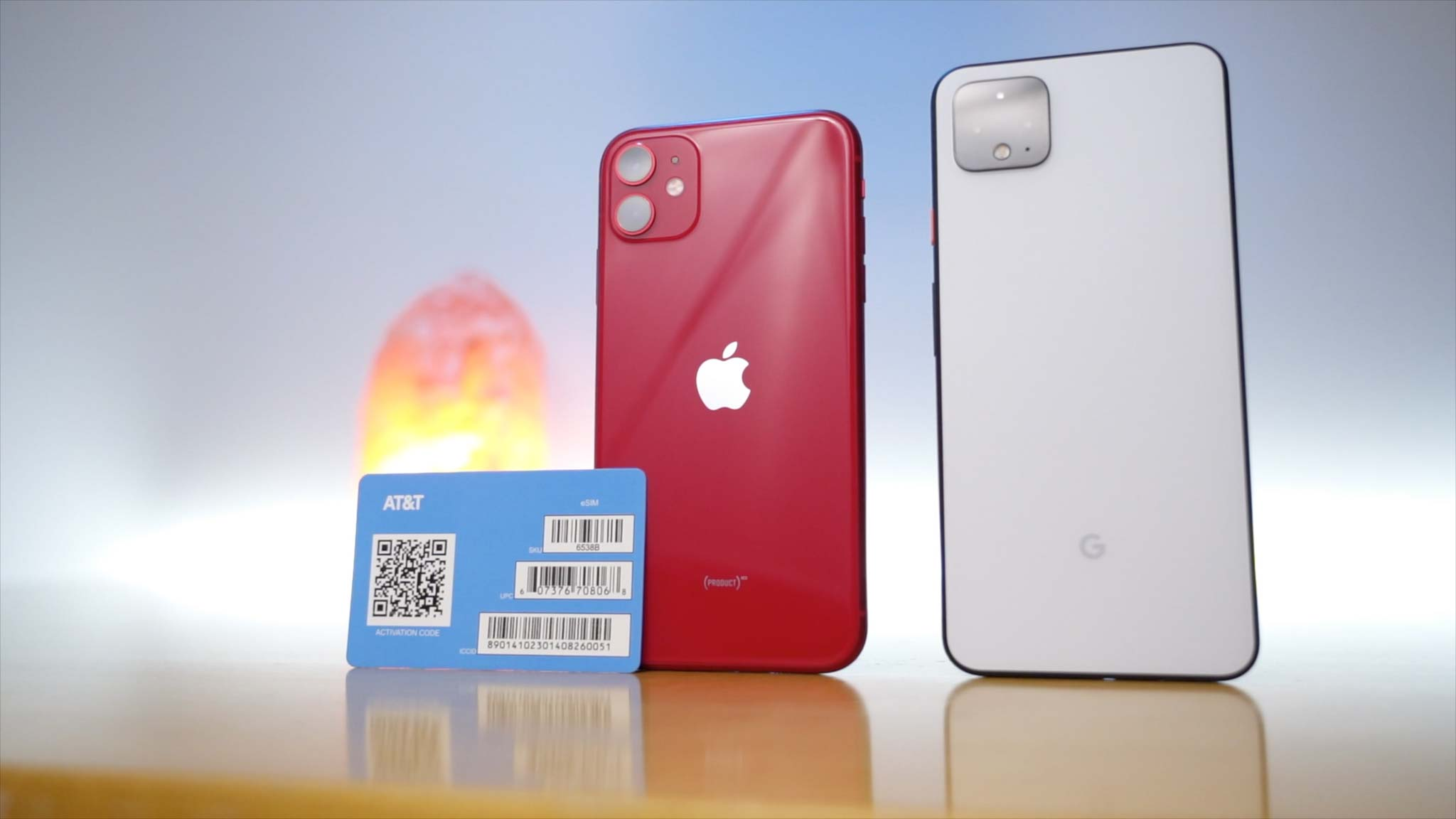 iPhone 11 in Product Red next to Clearly White Pixel 4 XL with AT&T eSIM card propped up on iPhone 11