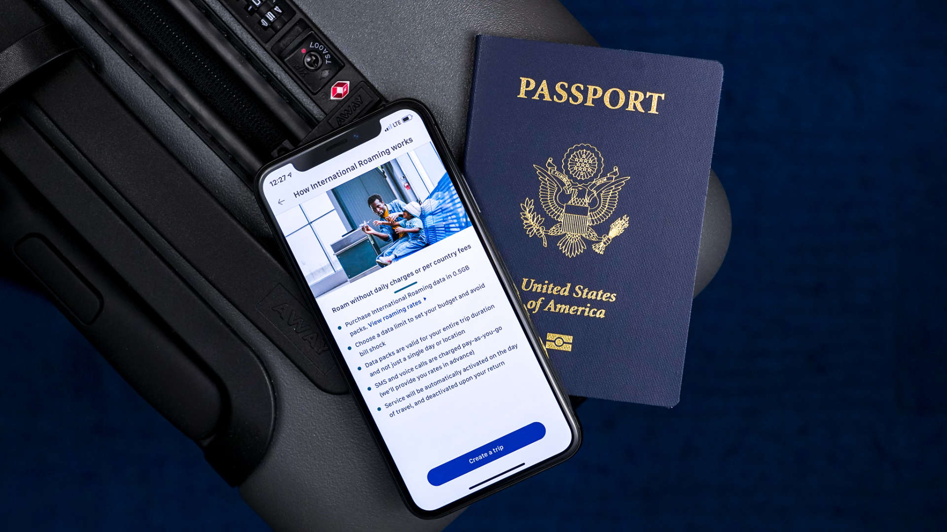 iPhone next to US passport on gray Away Luggage carry on suite case