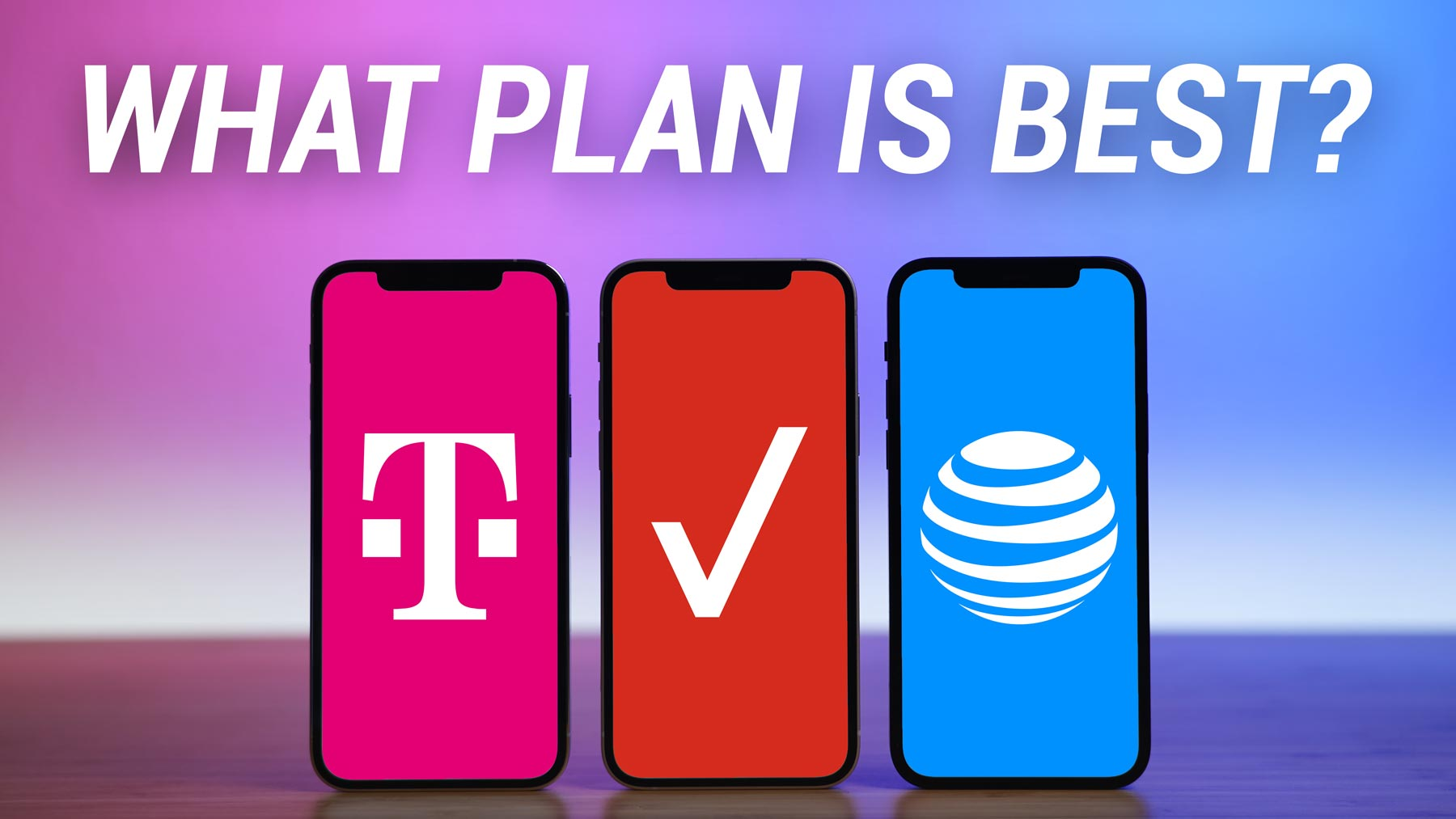 three iPhones standing vertically on desk with T-Mobile, Verizon, and AT&T logos displayed on screen