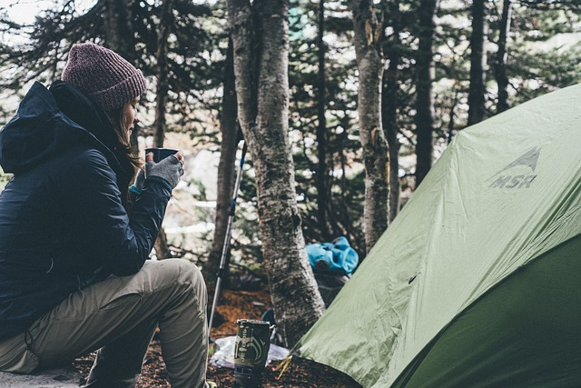 backpacker sipping coffee outside tent