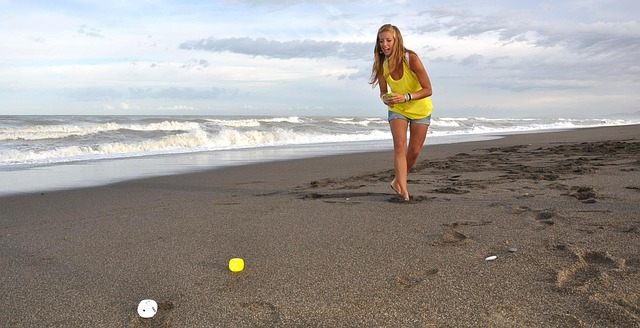 woman playing bocce ball at beach