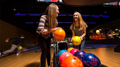 two teens holding bowling balls
